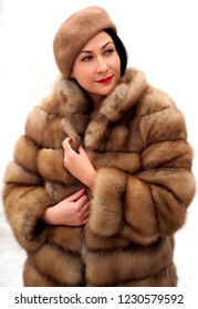 Fashion woman in a fur coat. Brown real fur