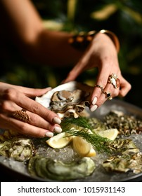 Fashion woman hands with expensive gold rings take oyster with lemon and dill