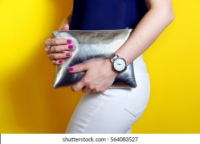 Fashion woman hold silver clutch in hand bag and watch near yellow background. Close up stylish accessory