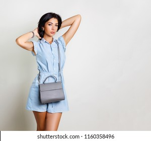 Fashion woman holding handbag wearing jumpsuit. Nice tanned brunette posing with lady handbag, studio shot on gray background