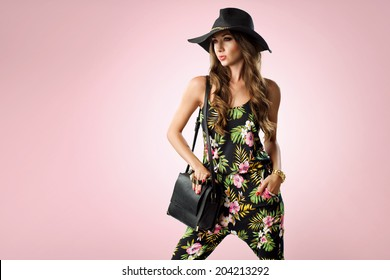fashion woman holding handbags wearing jumpsuit, hat, wedges shoes. Studio shot