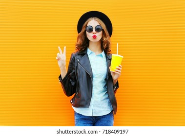 Fashion woman holds a cup of fruit juice, black rock jacket in the city on a colorful orange background