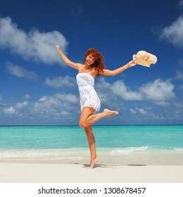 Fashion woman jumping on the beach. Happy island lifestyle. White sand, blue cloudy sky and crystal sea of tropical beach. Vacation at Paradise. Ocean beach relax, travel to Maldives islands