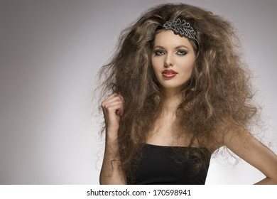 fashion woman with long brown curly hair style posing with pretty make-up and glitter accessory in the hair