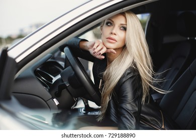 fashion woman in luxury car. young blonde girl portrait