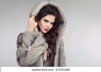 Fashion woman in mink fur coat, lady portrait. fashionable studio photo of gorgeous sensual brunette woman in mink hood