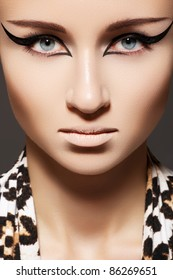 Fashion woman model with glamour make-up, cat eye liner makeup and scarf with leopard print. Vamp, wild cat style