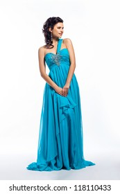 Fashion woman in modern fashion long blue dress posing. Formal party