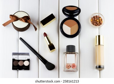 Fashion woman objects. Makeup and cosmetic set: lipstick, foundation, concealer, eyeshadow palette, blusher balls, perfume on white wooden background