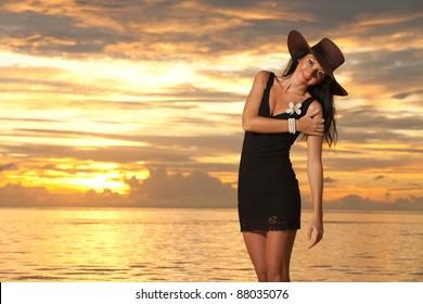 Fashion woman on the sea sunset background