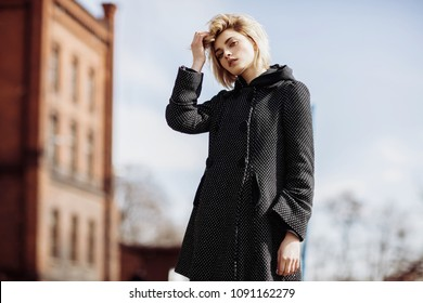 Fashion woman photo of young pretty girl touching her hair and posing outdoor in coat, spring street fashion