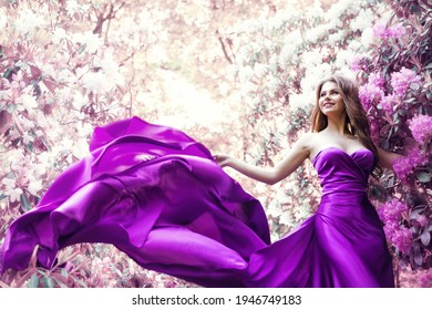 Fashion Woman Pink Dress in Spring Flower Garden. Beauty Model Girl in Purple Silk Gown Fluttering on Wind. Floral Pink Fantasy Background