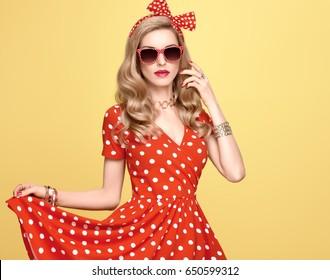 Fashion Woman in Polka Dot Summer Dress. Stylish Curly hairstyle, Trendy Headband, Sunglasses. Beauty Blond Pinup Model Girl. Glamour Playful Lady on Yellow.
