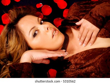 fashion woman portrait lying down over a dark background surrounded by red roses petals
