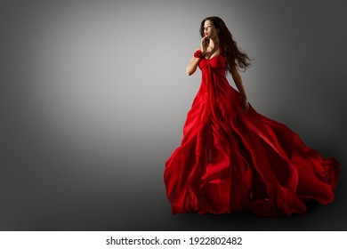 Fashion Woman in Red Dress. Beauty Model dancing in Long Evening Gown fluttering on Wind Black Hair flying in Air over Gray Background