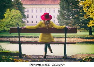 Fashion woman with red hat sitting on a bench in park and enjoying view on a castle, autumn season.