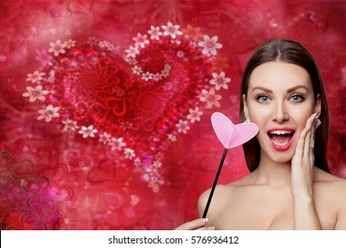 Fashion woman with red heart. Valentine's day art portrait. Beautiful make up and manicure. Surprised model girl face. Gorgeous glamour lady with bright makeup. Showing Heart