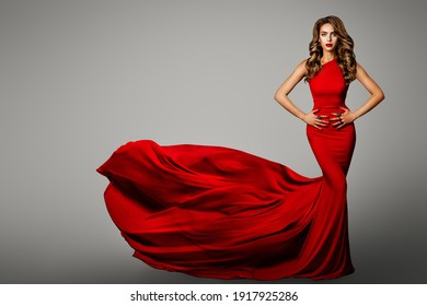 Fashion Woman in Red Tight Dress. Long Evening Red Gown waving on Wind. Beauty Portrait with Long Curly Hair. Gray Background
