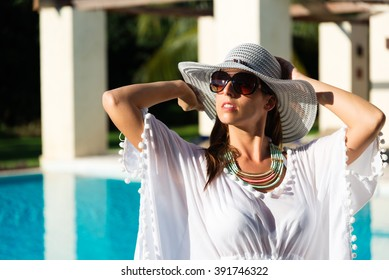 Fashion woman relaxing at luxury resort spa pool. Fashionable caucasian model wearing sun hat, sunglasses and white summer dress.