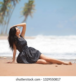 Fashion woman relaxing on the beach. Happy lifestyle. Sand, blue cloudy sky and ocean waves. Vacation at Paradise. Ocean beach relax, travel