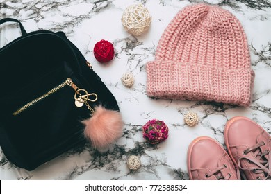 fashion woman set of velvet black backpack with pink fluffy keychain, sneakers and beanie hat on marble. flat lay, top view.