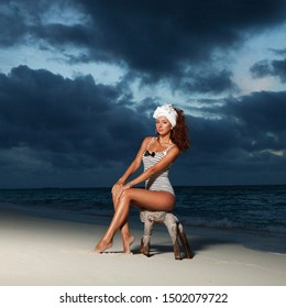 Fashion woman sit on the beach sunset background. Happy lifestyle. White sand, dawn cloudy sky and blue sea of tropical beach. Sexy tanned woman on the summer beach.