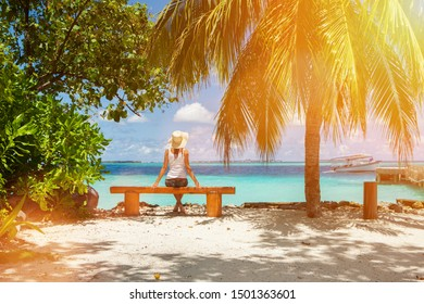 Fashion woman siting on a bench at the beach. Happy island lifestyle. White sand, blue cloudy sky and crystal sea of tropical beach. Vacation at Paradise. Ocean beach relax, travel to Maldives islands