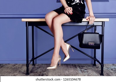 Fashion woman sitting on bench in black dress gold shoes and little bag. Blue wall