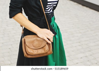 Fashion woman in striped T-shirt and green jacket. Fashionable woman in dress and coat with little leather brown handbag on the shoulder. Trendy clothes, street vogue look