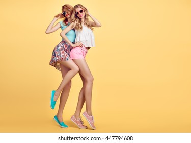 Fashion woman in Stylish Summer Outfit Having Fun. Hipster sisters best friends crazy cheeky Dance. Funny Girl in sunglasses. Glamour Trendy Hairstyle.Unusual Creative