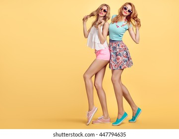 Fashion woman in Stylish Summer Outfit Having Fun. Hipster sisters best friends crazy cheeky Dance. Funny Girl in Fashionable sunglasses. Glamour Trendy Hairstyle.Unusual Creative