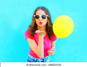 Fashion woman in sunglasses with yellow air balloon sends an air kiss over colorful blue background