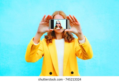 Fashion woman takes picture self portrait on smartphone on blue background