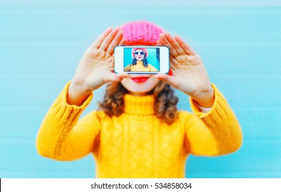 Fashion woman taking photo self portrait on smartphone over blue background in winter knitted colorful clothes