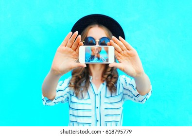 Fashion woman is taking photo self portrait on a smartphone in the city closeup screen over colorful blue background