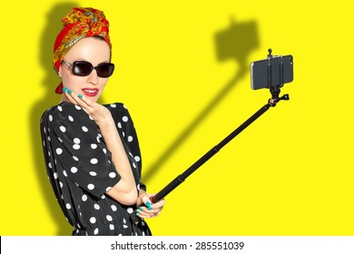 Fashion woman taking selfie over yellow background. focus on woman