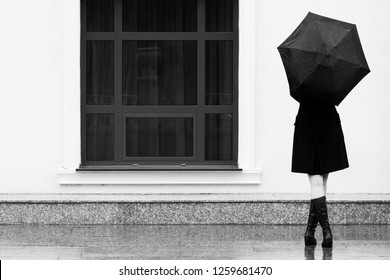 Fashion woman with umbrella walking on city street Stylish female model in black coat and long boots