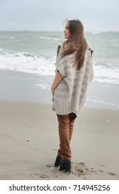 Fashion woman walking alone on a sea beach, casual oversize cloth, autumn outdoor