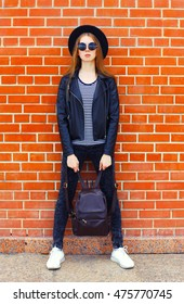 Fashion woman wearing a black rock style posing in city over bricks textured background