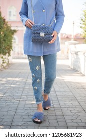 Fashion woman wearing blue jeans and cardigan with blue handbag in hand . Street style .