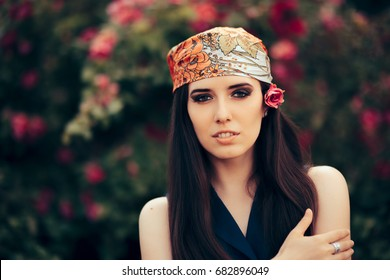 Fashion Woman Wearing Head Scarf in 70's Retro Style Outfit - Beautiful fashionista in stylish vintage look admiring a floral garden