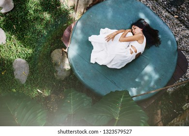 Fashion woman wearing natural white fabrics dress lying outdoor on mattress swing in jungle forest resort