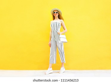 Fashion woman is wearing a white striped pants, round hat posing on colorful yellow background