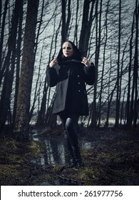 Fashion woman wearing a winter coat and she standing in a gloomy forest, cold rainy weather, cross processed full length image