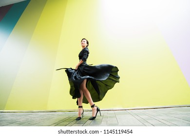 Fashion woman. Young beautiful chinese girl dancing outdoor wearing long black dress with high heels over colorful wall background. Stylish trendy lady.