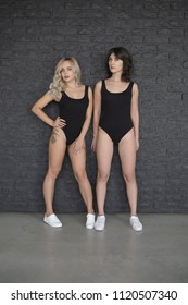 Fashion Women In Black Swimsuit With Perfect Natural Makeup On Gray Brick Background. Beautiful Female Models With Tanned Healthy Skin And Sexy Fit Body In Stylish Swimwear. Blonde and Brunette Models