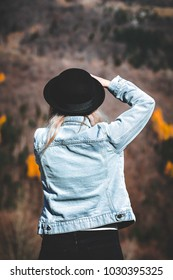 Fashion women photographer taking amazing landscape pictures. She's wearing a nice casual outfit with blue denim jacket, black jeans and a hat.