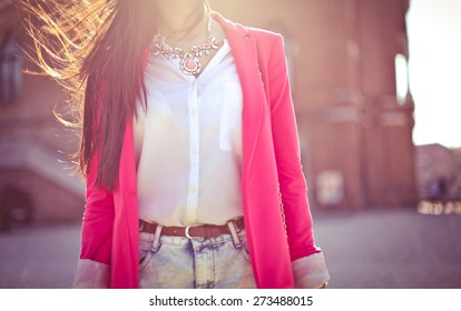 Fashion women in pink blazer with the sun in the background