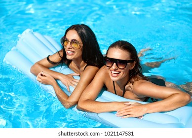 Fashion Women Swimming In Pool In Summer. Happy Sexy Girls In Stylish Swimsuits And Trendy Sunglasses Relaxing In Swimming Pool Water, Having Fun And Enjoying Travel Vacation. High Quality Image.