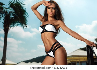 Fashion Women Swimwear. Beautiful Woman Model With Fit Sexy Body, Tanned Skin In Stylish Fashionable White Black Bikini, Sky On Background. Hot Girl At Luxury Resort Hotel In Summer. High Resolution